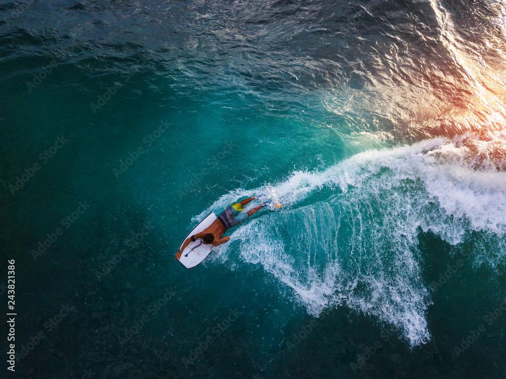 Fototapeta Bodyboard surfer rides tropical wave at sunset