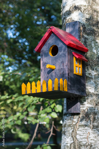 Bird house with red roof, yellow window and fence on birch close up Fototapet