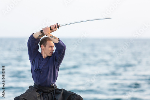 Fotografie, Obraz  Young Iaido fighter master of martial arts exercises in a concentrated manner ho