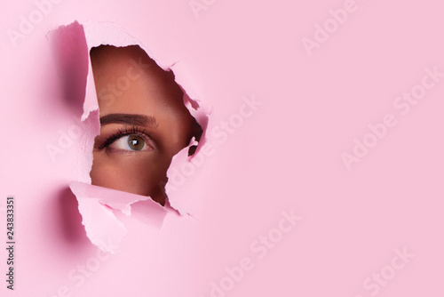 Pinturas sobre lienzo  Girl with bright eyes make up looks through hole of pink paper