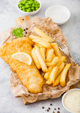 Traditional British Fish And Chips With Tartar Sauce On Chopping Board With Fork And Green Peas On White Stone Table Background.