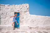 Fototapeta Uliczki - Girl in blue dresses having fun outdoors on Mykonos streets