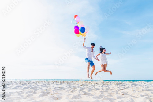 Photo Happiness lover couple holding colorful balloons and jumping with smile on the tropical beach in sunny day