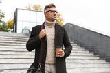 Fototapeta  - Image of mature man 30s wearing eyeglasses, walking through city street and holding takeaway coffee