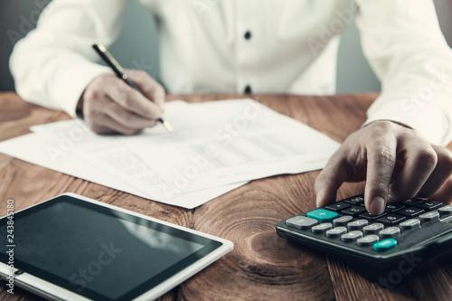 Businessman using calculator in his desk. Fototapet