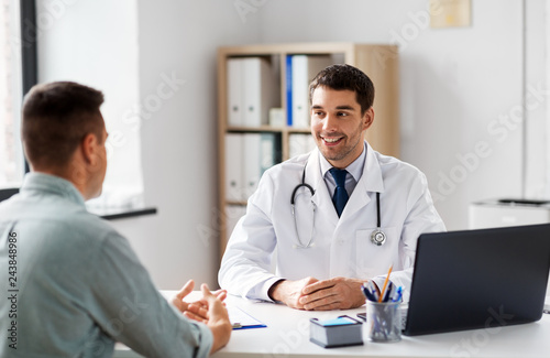 medicine, healthcare and people concept - smiling doctor talking to male patient at medical office in hospital