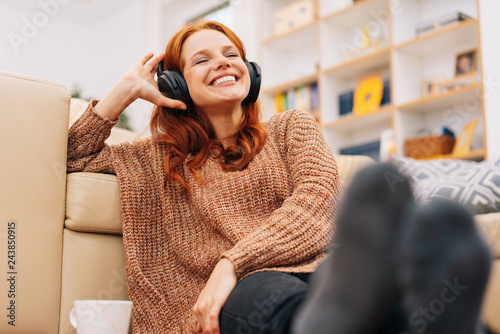 Foto  Woman relaxing at home with headphones