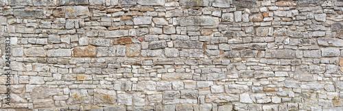 Fototapeta premium Panorama - Stara szara ściana grubej, wielu małych, prostokątnych ociosanych kamieni naturalnych