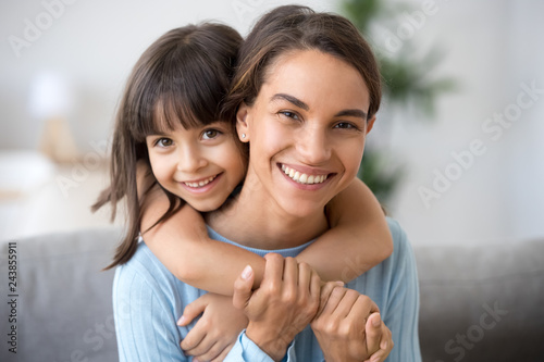 Beautiful family of single young mom and cute preschool kid daughter embracing mommy looking at camera, happy loving mother piggybacking smiling little child girl hugging mum headshot portrait
