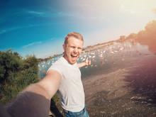 Tourist Man Making Selfie Photo Action Camera On Background Of Flamingo Birds, National Park Of France