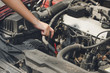 Beautiful girl hands open the car skirt to check the oil level of the car. The concept of engine maintenance Travel safely Caring for old cars