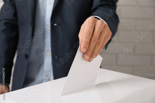 Foto op Plexiglas Historisch geb. Man putting his vote into ballot box against brick wall, closeup