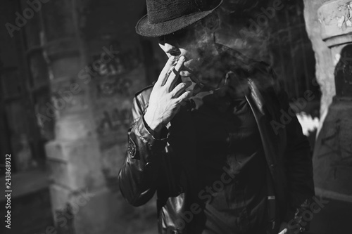 Fotografia  A man with a cigarette in a hat and a raincoat on the street of a night city