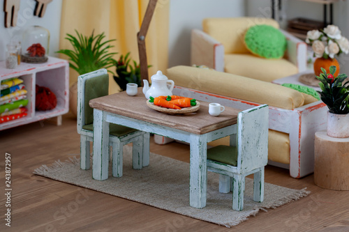 Photo  Interior of a dollhouse, dining area with table served for tea and two chairs