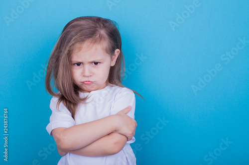 Fotografía  The little girl on a blue background was offended by folding her arms and frowni