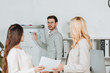 side view of businesswomen holding papers and looking at handsome businessman in eyeglasses pointing at whiteboard