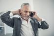 Beaming elderly man speaking by the phone
