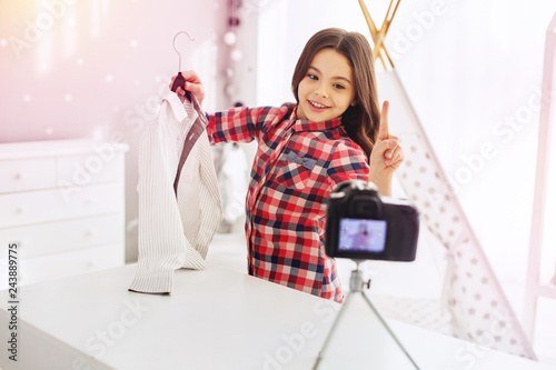 Fotografie, Obraz  Dark-eyed little fashion blogger recommending her favorite clothes shop
