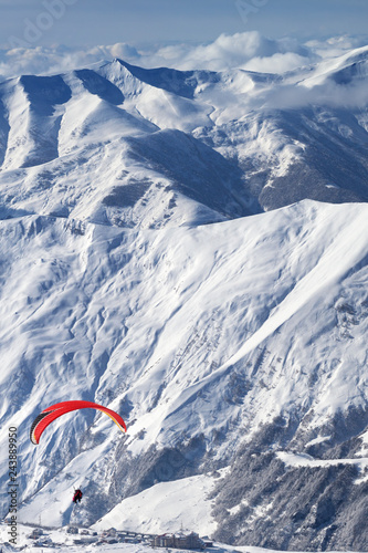 Paragliding at snowy mountains over ski resort at sunny day