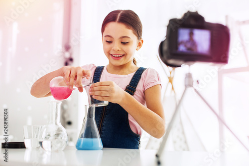 Little girl wearing jeans jumper suit making chemistry experiment