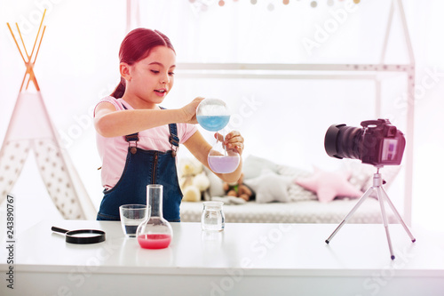 Fotografija  Dark-haired blogger filming video about chemistry in her living room