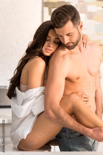 Fototapeta selective focus of beautiful seductive couple hugging at home