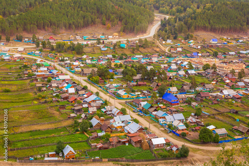 Fotografie, Obraz  Top view of the Ural village STAROSUBHANGULOVO surrounded by the river Belaya among mountain peaks and taiga