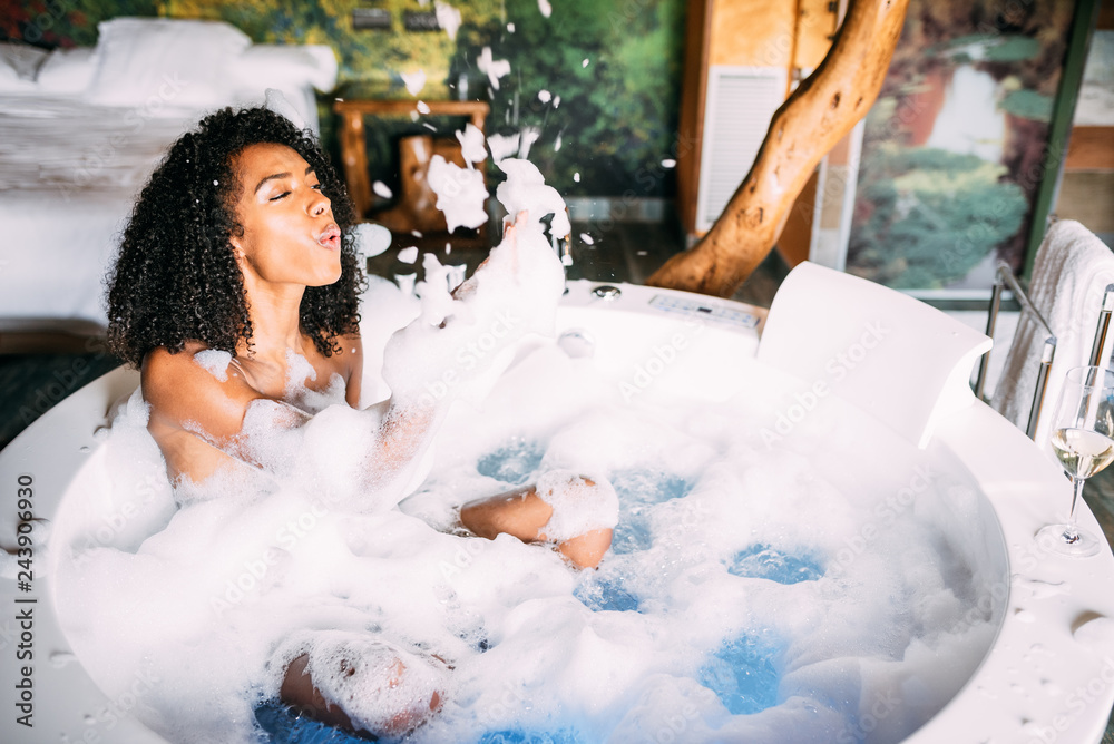 Fototapeta Woman relaxed in the jacuzzi covered in foam