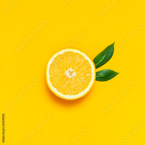 Ripe juicy orange and green leaves on bright yellow background. Orange fruit, citrus minimal concept, vitamin C. Creative summer food minimalistic background. Flat lay, top view, copy space.