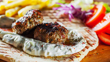 Spicy Bifteki, Frikadelle Or Frikkadel Meatballs With Minced Beef And Lamb With Pita Bread, Tzatziki Dip, Vegetables Salad And French Fries. Greek Meatballs Keftedes Or Keftedakia.