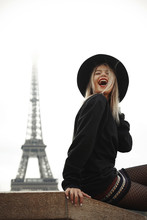 Woman In Black Hat In Paris On Background Of The Eiffel Tower.