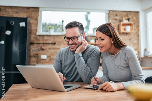 Fototapeta Smiling couple using laptop at the kitchen table.