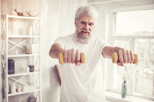 Fényképezés Positive delighted mature man doing morning exercise