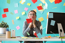 Stressed Young Business Woman Looking Up Surrounded By Post-its In The Office.