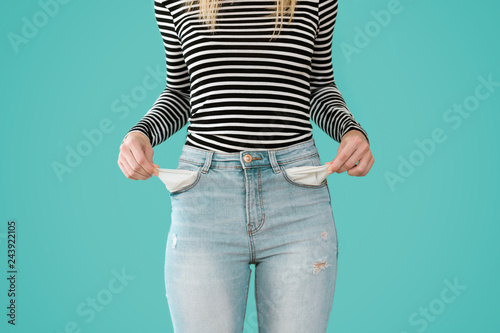 Photo Young woman showing doesn't has nothing in her jeans pockets on blue background