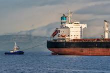 Tugboat Pulling A Cargo Ship
