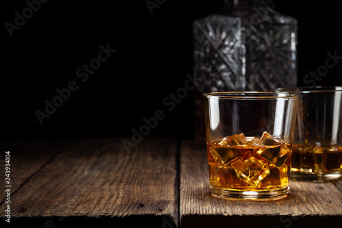 Photo Two glass of whiskey with ice and crystal decanter on wooden table