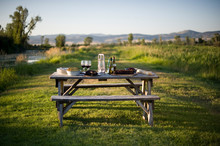 Picnic Table On Green Grass With Blue Sky, Trees And Hills In Summer Evening Sunlight