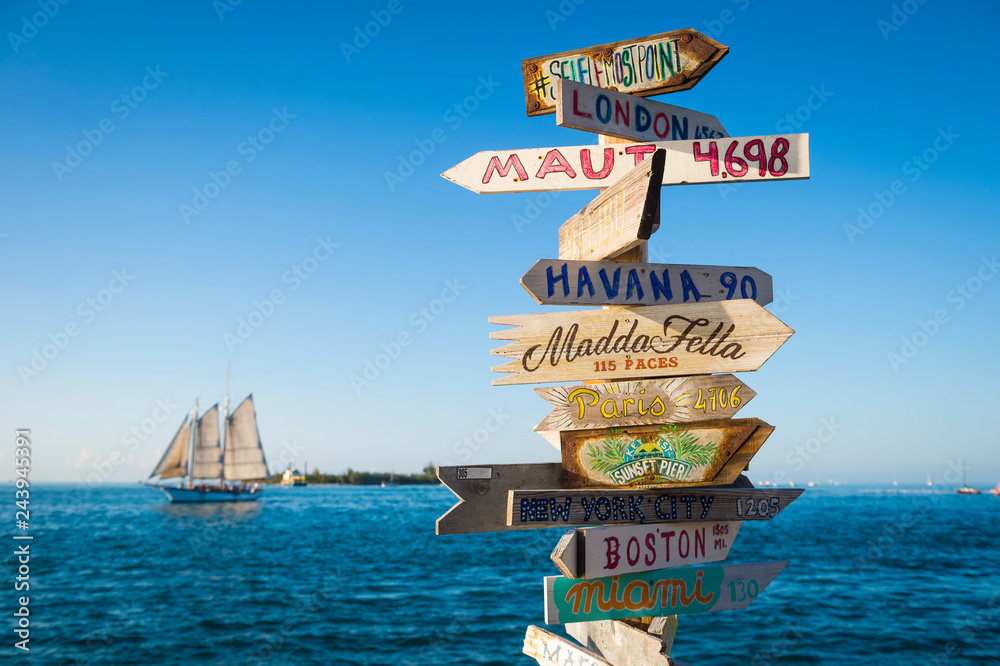Fototapeta Bright scenic view of rustic wooden direction sign with sailboat in Key West, Florida, USA