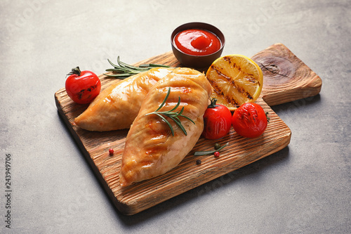 Wooden board with tasty grilled chicken breasts and garnish on table