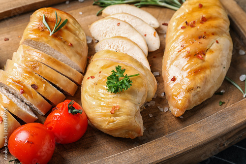 Fried chicken breasts and tomatoes served on wooden board, closeup