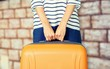 Woman hands holding travel suitcase