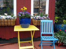 Flower Window Boxes And Brightly Painted Chair And Table