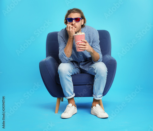 Emotional man with 3D glasses and popcorn sitting in armchair during cinema show on color background