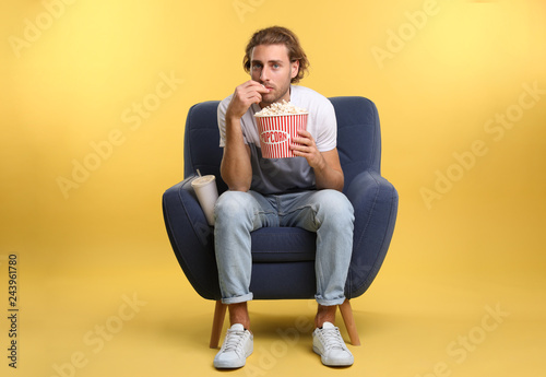 Fotografie, Obraz  Man with popcorn and beverage sitting in armchair during cinema show on color ba