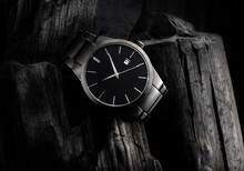 Luxury Black Metal Wristwatch, On Top Of A Pile Of Coal, With Lots Of Contrast And Texture