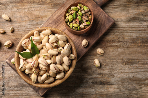 Organic pistachio nuts in bowl on wooden table, flat lay. Space for text