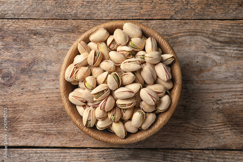 Organic pistachio nuts in bowl on wooden table, top view