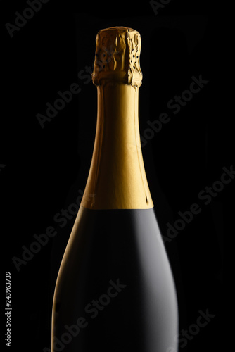 Unopened bottle of Champagne against a black background