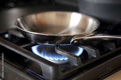 Stainless steel pan heating up on gas range stove.